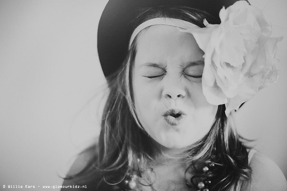 blond meisje met bloem in het haar en zonlicht