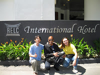 The band members posing in front of the RELC International Hotel