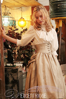 A girl in a tan full, bustled skirt and white shirt with a simple jabot stands in a steampunk tent