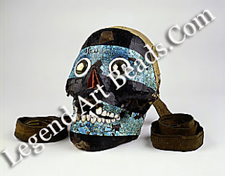 back ornament. Human skull set with mosaic of turquoise and lignite, having eyes of iron pyrites circled by white shell, and a movable jaw. Mixtec, of Aztec period. W. 14.5 cm. Museum of Mankind. London