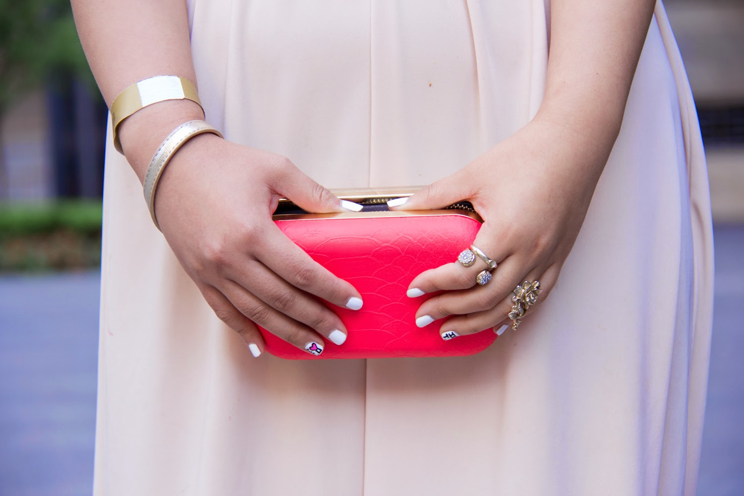 nude-maxi-dress-pop-of-orange, neon-clutch, gold-rings
