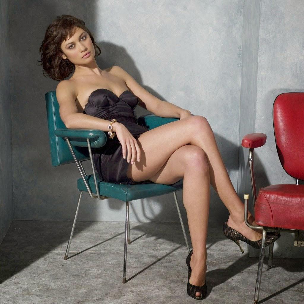Olga Kurylenko sitting wit her sexy legs crossed