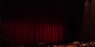 Das Bild zeigt eine Theaterbühne mit heruntergelassenem Vorhang - das Publikum wartet bereits gespannt auf den Beginn des Theaterstücks.