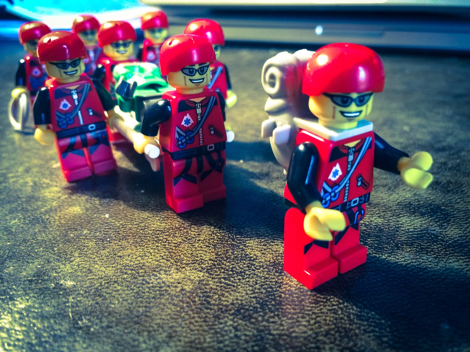 Eight Lego Mountain Rescue figures carrying a lego casualty on a stretcher.