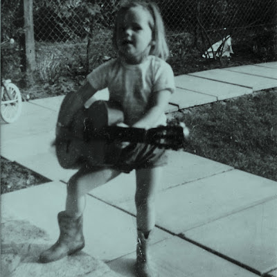 1970s snapshot of child in cowboy boots, playing guitar