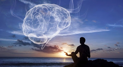 Picture of someone in lotus meditation pose reaching out and touching the sunset in the background.  Image of a human brain superimposed on the sky.