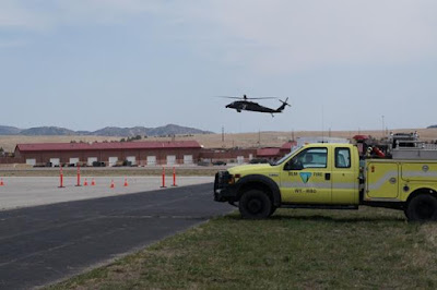 A BLM engine waits for a military helicopter to land before navigating the Evasive Driving Course.