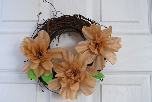 Small flower wreath on a door with spring green leaves added.
