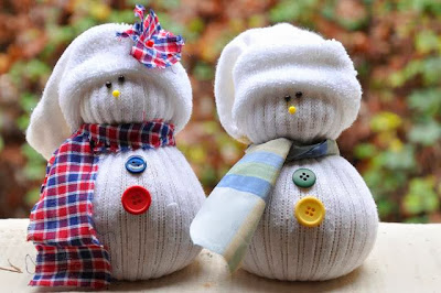 Two snowmen made out of athletic socks and decorated with fabric scarves and buttons