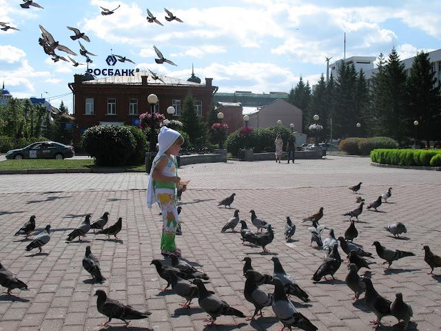 Настя на площади Ленина в Томске. Солнечный день, голуби в небе