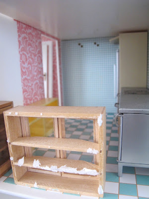 Interior of the bathroom of a half-built Lundby dolls' house. In the room are a selection of kitchen fittings.