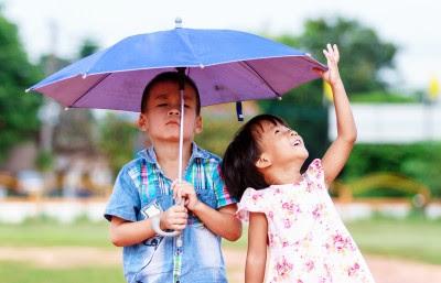 NAMC Montessori homeschool develop social skills boy and girl under umbrella