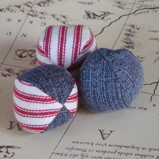 Hacky sacks made out of solid-blue and red-and-white striped denim