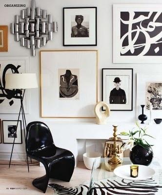 decoracion noridca y vintage en blanco y negro en el salo con silla panton y composicion de cuadros en las paredes