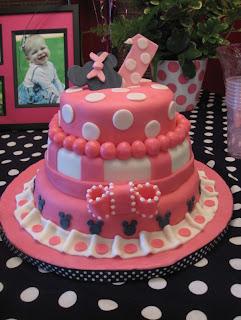 minnie mouse con un lindo pastel y decoraciones la fiesta sera todo un