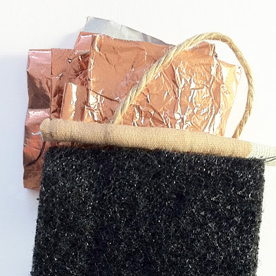 A colour swatch taken from household objects includes a plaster, some copper chocolate wrapper, a piece of string and a black pan scrubber.