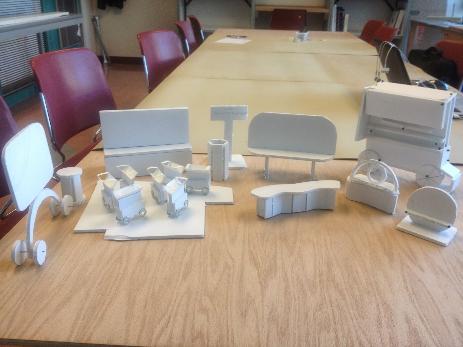 A number of foam core model mockups are organized on a table and the image is taken at a waist height angle.