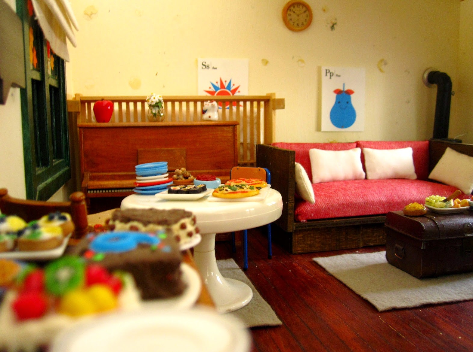Selection of miniature dolls' house party food arranged in a living area, ready for a party.