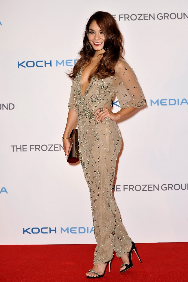 Vanessa Hudgens pairs her Jenny Packham jumpsuit with a gold box clutch and black stilettos