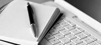 black and white photo of a pad and pen on top of a computer keyboard
