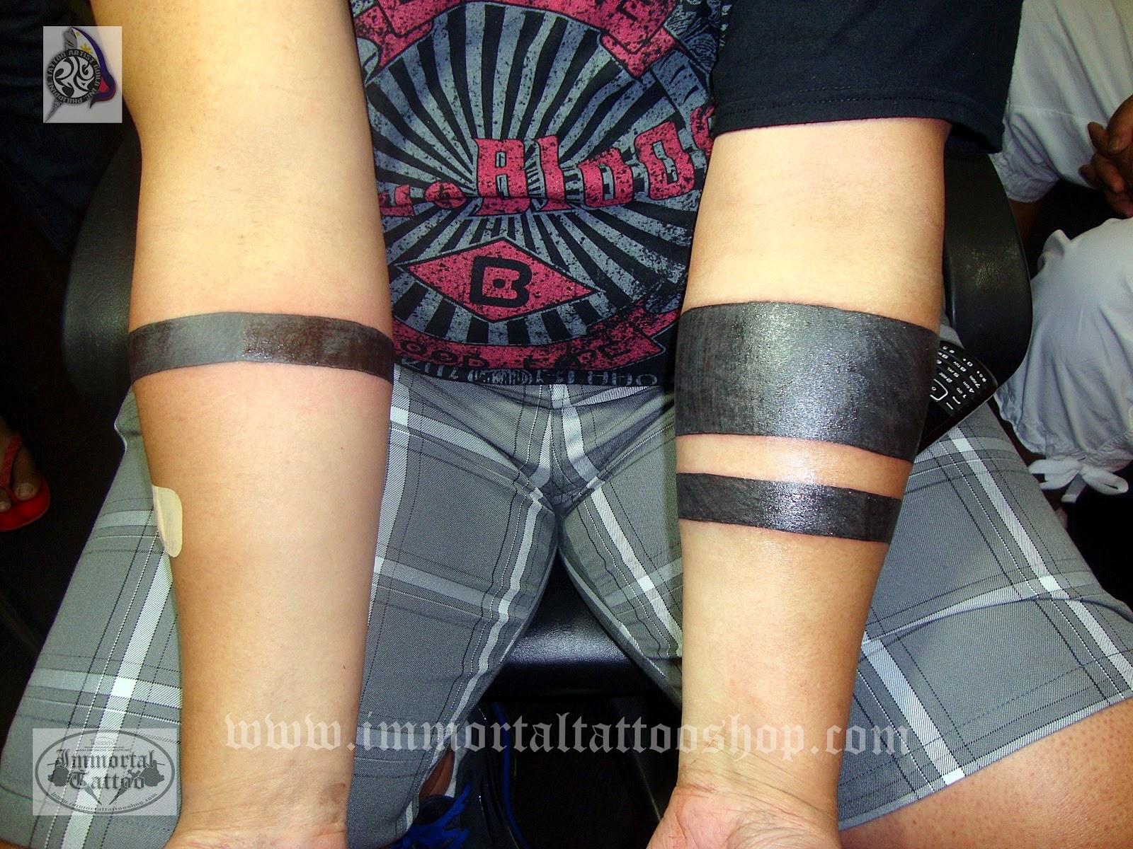 Что означает черная полоса на руке тату