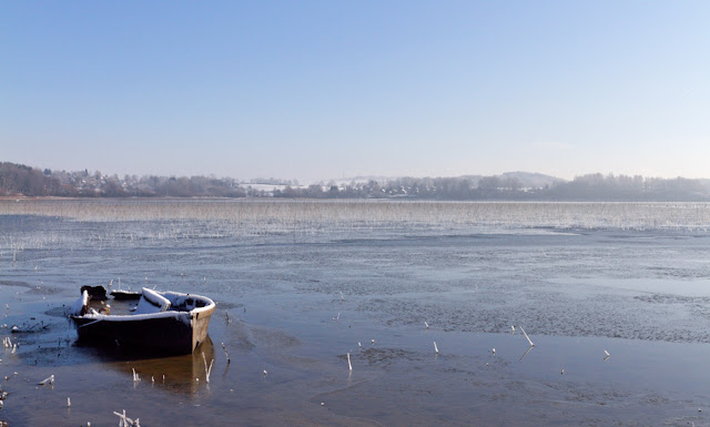 Vergane glorie, kapotte roeiboot op een verstild meer