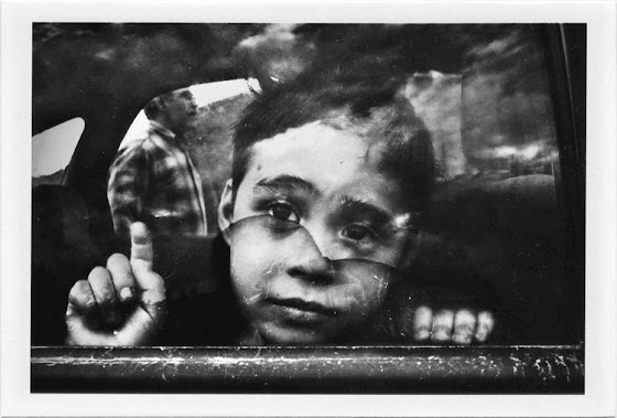 dirty photos - et - a black and white photo of a little boy in car and photographer's reflection