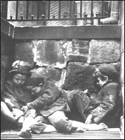 Two poor, homeless children sleeping in an alley