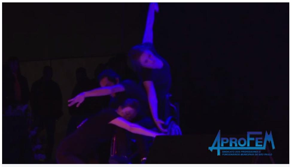 Descrição da Foto: Três intérpretes dançam entrelaçando seus corpos com os braços estendidos em diferentes direções. Uma em pé, outro na cadeira-de-rodas e outra com a cabeça apoiada no colo do cadeirante. Estão sobre um foco de luz azul.