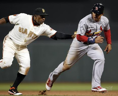 San Francisco Giants shorts stop Miguel  Tejada (L) tags out St. Louis Cardinals baserunner Jon  Jay (R) after Jay attempted to steal second base during the top of the eighth inning of their MLB National League baseball game in San Francisco, California, April 9, 2011.   REUTERS/Beck Diefenbach
