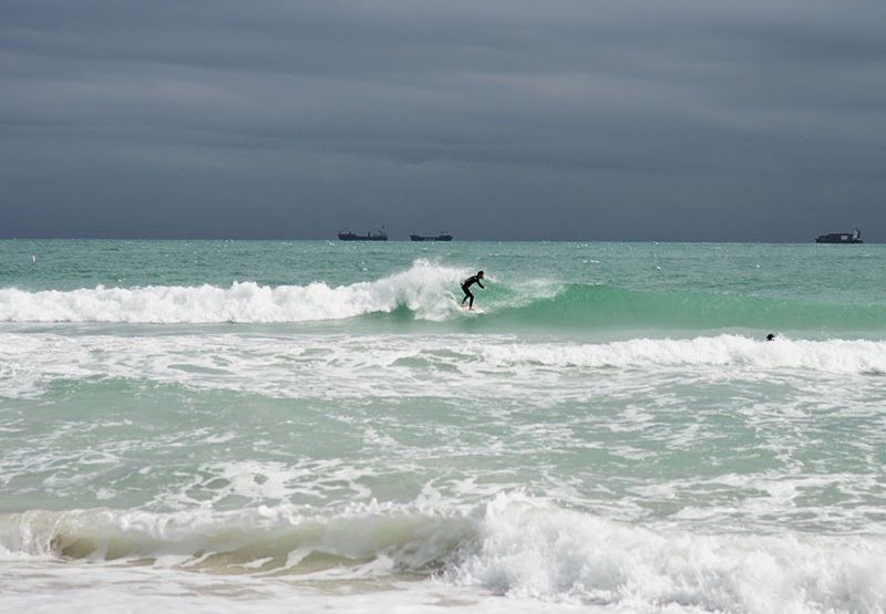 Miami beach surf scene with surfers surfing in the waters of South Pointe park and beach