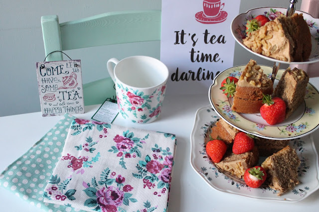 white table with cake and strawberries on cake stand, floral mug and tea towels sign saying it's tea time darling