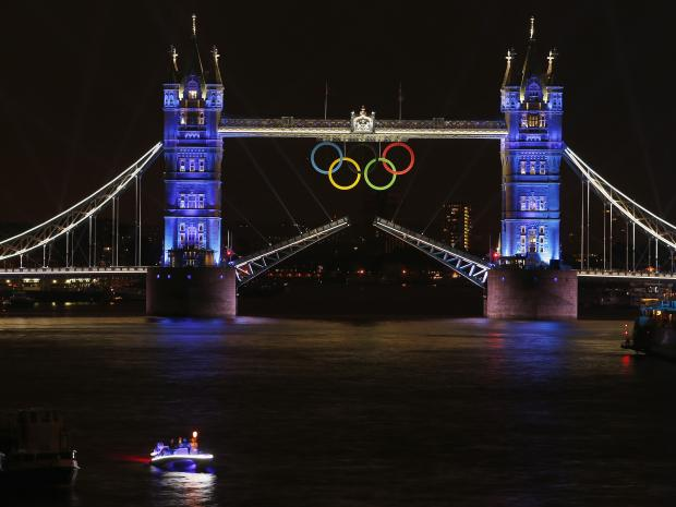 The Olympic rings hang on London's Tower Bridge as a speedboat driven by Britain's David Beckham and carrying the Olympic torch prepares to mark the opening ceremony of the 2012 Olympic Games REUTERS/PAUL HANNA