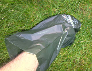 Shows how to pick up dog waste in grass with a Mutt Mitt