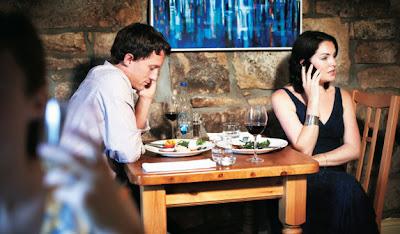 Foto de um casal a mesa de um restaurante, cada um falando em seu próprio celular