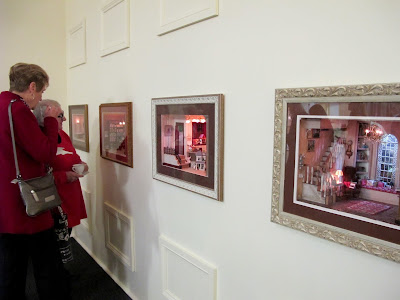 Customers admiring dolls' house miniature room boxes set into the wall.