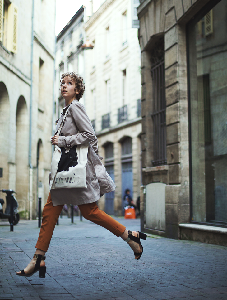 head to foot das sheep photography, running in the street in trench coat, with a tote bag and orange pants