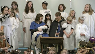 Angels sing to baby Jesus at manger in Christmas pageant