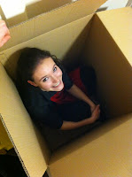 Photo of a cute French girl hiding inside a large box
