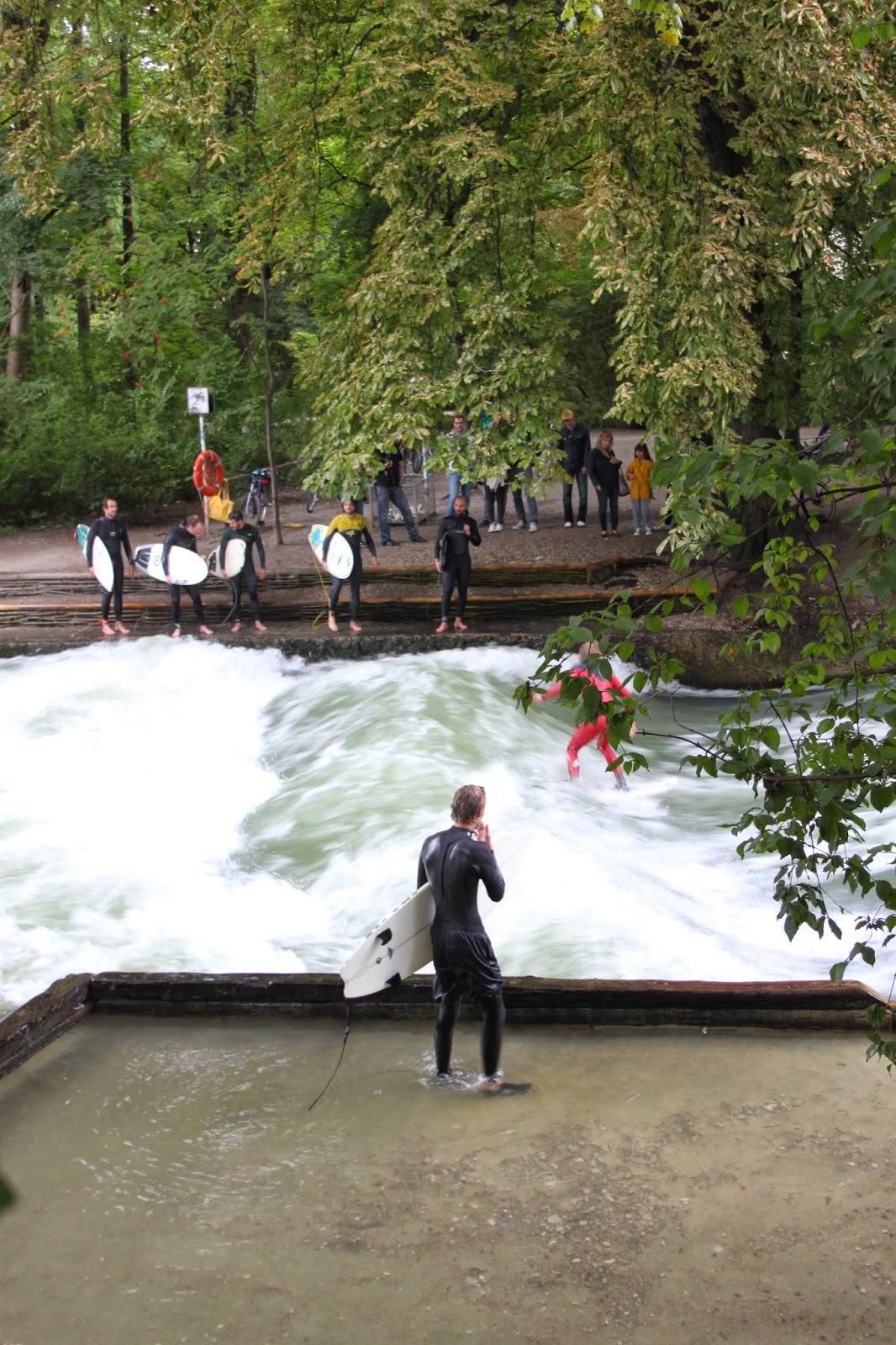 Surfer auf der Eisbach-Welle im Englischen Garten, München