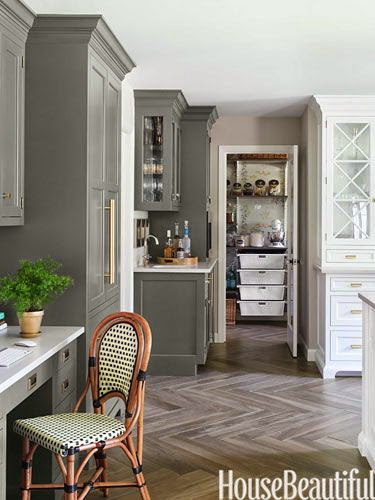 traditional kitchen with soft brown beige hard wood floors in chevron pattern gray painted and white glass front cabinets