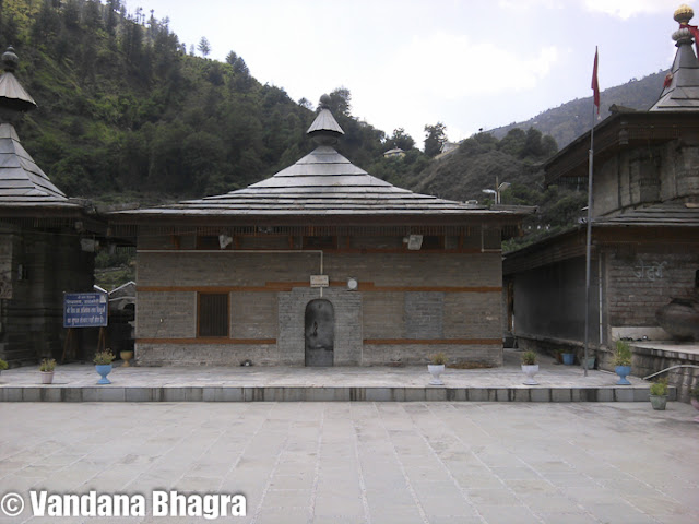 """Hatkoti Temple: Simplistic yet mesmerizingVandana Bhagra, ShimlaPhotos: By meEqually famous by both names, the Hatkoti Temple or the Hateshwari Temple, a winding downhill drive of about 30 kms from Kharapatthar will take you to this ancient temple built during the Gupta period in Nagara style, with a pagoda type structure during the seventh century. This temple is dedicated to Goddess Durga, in the form of Mahishasurmardini, also known as Mata Hateshwari. With her eight arms she is seen riding a lion as she pierces the heart of the Mahisha demon, whose human form emerges from the severed neck of the buffalo. According to the style followed in the hills, the garbhagriha (sanctum sanctorum) is naturally dark but the idol of the goddess is elegantly cast in bronze, which emits a soft, unearthly glow. A walk inside the temple will make you gaze at the intricate architectural designs depicted on the walls. On both sides of the idol one can see Bhrami scripture, which has yet to be deciphered and no one knows what it means.  Along the River Pabbar, the easiest way to reach this temple from Shimla is via Theog, Chailla, Kotkhai, Kharapatthar, taking approximately five hours covering a distance of almost 104 kilometers. One can always stop mid-way to enjoy the beauty of the hills but once the downhill journey starts you can hear the river flowing below and the beautiful temple complex in full view to capture your breath. At Hatkoti, two other small mountain streams Bishkalti and Raanvti join the Pabbar and locals believe that the color of the Bishkalti is somewhat grayish as the stream oozes poison. With the convergence of the three water streams Hatkoti has now became a famous pilgrimage. The local priest says, """"This is a very sacred place and immensely revered by the locals and orchardists as whenever the first lot of apples is plucked people always stop here to pay their respect and make offerings to the deity. An interesting thing about the Devi's idol is that you can s"""