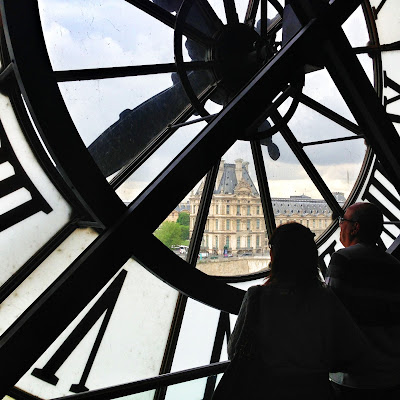 Looking through the clocks at Musee d'Orsay to the Louvre in Paris France