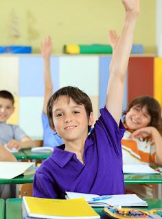 Elementary school students raising hands in classroom.