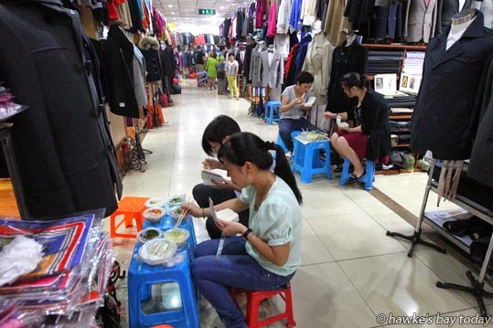 Retailers eat in the aisles of a shopping mall, which is split up into hundreds of booths photograph