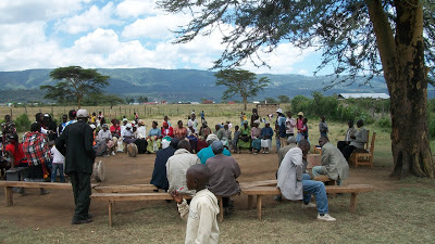 The people gathered under the tree to have church in an empty lot in the IDP camp.
