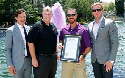 "Crown Royal's ""Your Hero's Name Here"" winner and Brickyard 400 race namesake, U.S. Marine Corps Sergeant Jeff Kyle, center right, is honored by Indianapolis Mayor Greg Ballard, center left, and Indianapolis Motor Speedway President Doug Boles, left, and Crown Royal Brand Director Matt Pechman with the proclamation of Jeff Kyle Day in Indianapolis, Friday, July 24, 2015. (AJ Mast /AP Images for Crown Royal)"