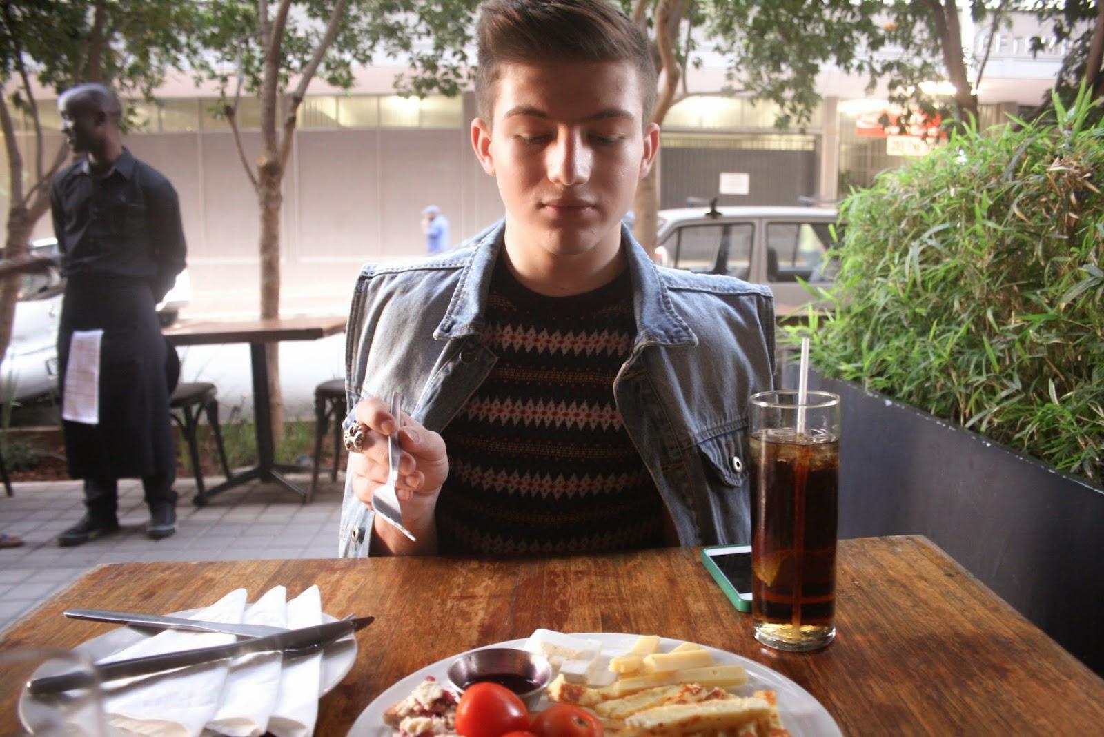 josh having a cheeseboard and ice tea at pata pata maboneng