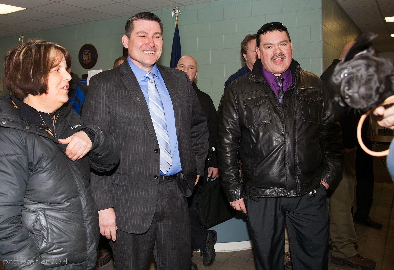 A short woman with short brown hair is standing on the left side. Next to her is a man in a suit, he is the warden. Next to him is another man with a mustache and a black leather jacket. On the far right side is the out-of-focus face of a small black lab. Photo bomb!