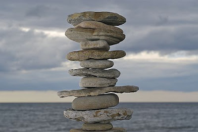 rock cairn balanced against blue sky and sea background